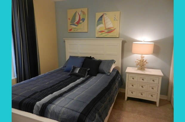 Queen bed in guest room with nautical theme